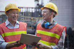 Two engineers in protective workwear standing and laughing outside of a factory Stock Photos