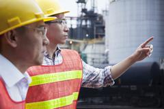 Two engineers in protective workwear pointing outside of a factory - stock photo