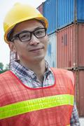 Portrait of smiling young engineer in protective workwear outdoors in a shipping Stock Photos