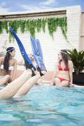 Four friends sitting in the pool, feet with flippers in the air - stock photo