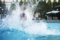 Young man jumping into a pool with water splashing all around him - stock photo
