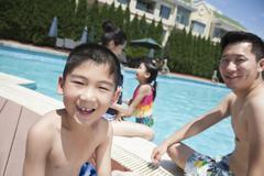 Cute little boy and his family playing in the pool - stock photo