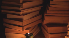 Pan right stack book library row candle light bookstore bookshelf series night Stock Footage