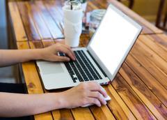 close-up image of female hand writing on laptot - stock photo