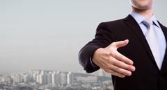 Portrait of young business man extending hand to shake over a cityscape Stock Photos