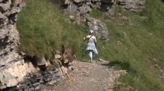 Woman nordic walking on Alpine mountain path over Oeschinen lake, Switzerland. Stock Footage
