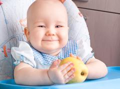 baby with yellow apple - stock photo
