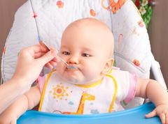 Stock Photo of little baby feeding with a spoon