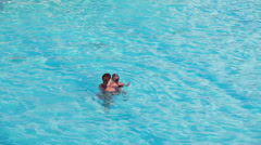 Small child swimming with parents in pool Stock Footage