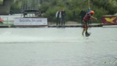 Professional wakeboarder performing tricks summersault tow cable, click for HD Stock Footage
