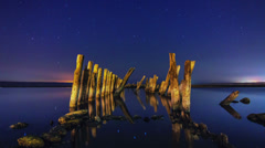 Timelapse of a starry night with wooden columns and firth water in the foregroun Stock Footage