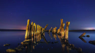 Stock Video Footage of Timelapse of a starry night with wooden columns and firth water in the foregroun
