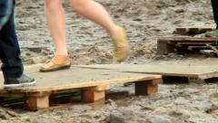 People step on wooden platform walking over dirty place, click for HD Stock Footage
