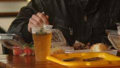 Man in fastfood restaurant eating potato chips burgers meat beer, click for HD Stock Footage