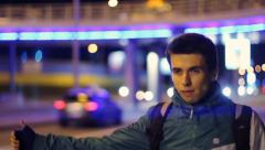 Young adult male tourist catches cars, night hitch-hiking, bag, click for HD Stock Footage