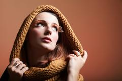 Stock Photo of Young creative make up woman with false long orange eyelashes and warm scarf