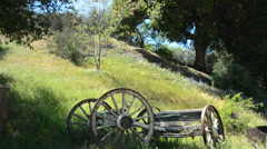 Old cart against a grassy hill Stock Footage