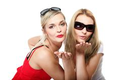two young women blowing kisses to the camera - stock photo