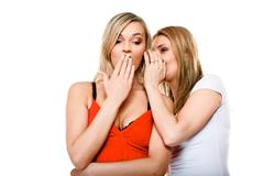 gossiping friends, two women sharing a secret - stock photo