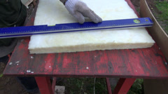 Worker cut mineral rockwool material for wall insulation Stock Footage