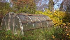 Old primitive plastic greenhouse in autumn farm garden Stock Footage