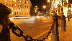 Evening city street, cars drive, yellow red lights, chains posts, click for HD Stock Footage