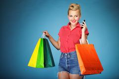 Stock Photo of girl with shopping bags and cell phone retro style