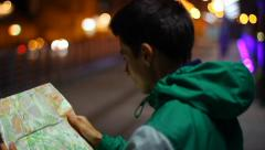 Tourist searching place location in map, lost in city night, click for HD Stock Footage