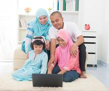 Malay indonesian family surfing internet at home. Stock Photos