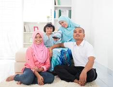 Malay family watching television enjoying quality time Stock Photos