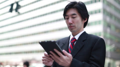 Asian businessman in New York City using tablet pc iPad Stock Footage