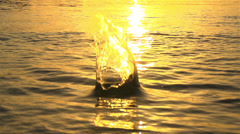 SLOW MOTION:Throwing a stone in the water at sunset Stock Footage