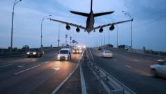 Airplane landing above city highway, transportation traffic dusk, click for HD - stock footage