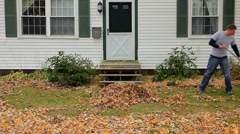 Man raking fall leaves in his front yard, stops and smiles at camera Stock Footage