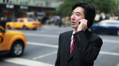 Asian businessman calling talking on cellphone in New York City - stock footage