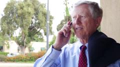 Senior Business Man Talks on Cell Phone Suit Slung over Shoulder Close Up - stock footage