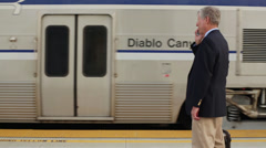 Senior Business Talks on Cell Phone Foreground while Train Departs - stock footage