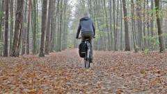 Cyclist in autumn / fall forest Stock Footage