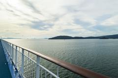 Railing facing to island with blue skies Stock Photos