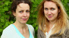 Two young woman look and smile against green foliage Stock Footage
