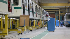 Workers assemble trains at workshop in factory Stock Footage