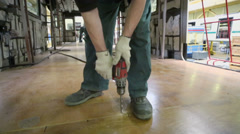 Worker drills wooden floor during assemblage of train Stock Footage