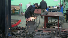 Worker grinds metal part for train wagons at factory Stock Footage