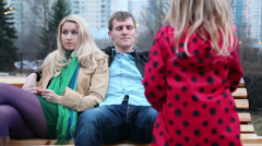 Young couple sit on bench and father checks clothes Stock Footage