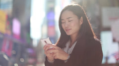 Asian woman in New York City Times Square texting smart phone Stock Footage