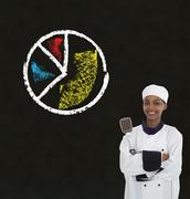 african american woman chef holding spatula with chalk pie chart on blackboar - stock photo