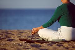 Stock Photo of mature woman doing yoga on sandy beach