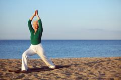 Mature woman stretching on the beach Stock Photos