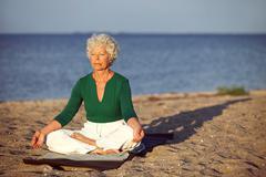 elderly woman on beach meditating by ocean - stock photo