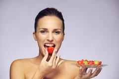 beautiful young caucasian woman eating healthy fruits - stock photo